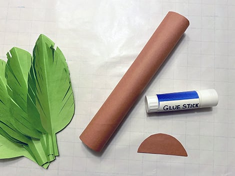 gluing brown construction paper onto the paper towel roll and cut-out semi circles