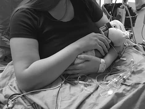 Mom and baby cuddling in the NICU.