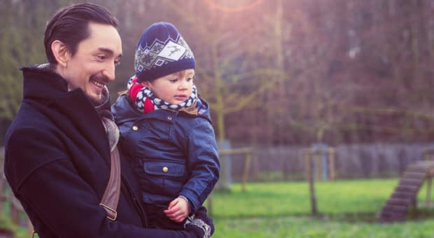 Father holds young son in arms as they focus on something off-camera.