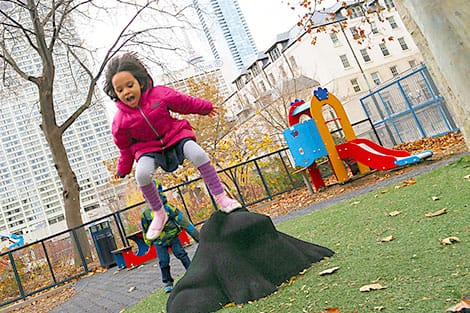 Happy little girl jumping in an urban playground.