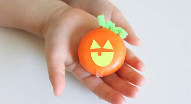 A child holding a babybel cheese jack-o' lantern.
