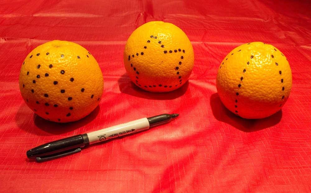 Three oranges with designed drawn on them.