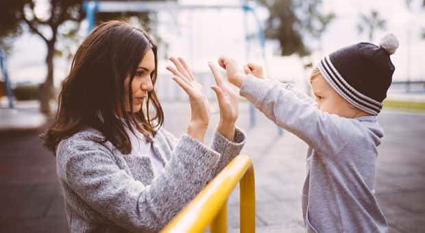 A mother and son playing outdoors at a playground.