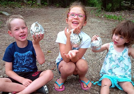 Three kids holding orange-muffins wrapped in foil with small handles on the top.