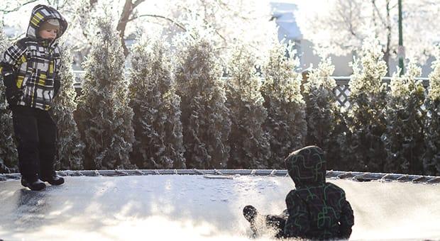 Children playing on trampoline in winter