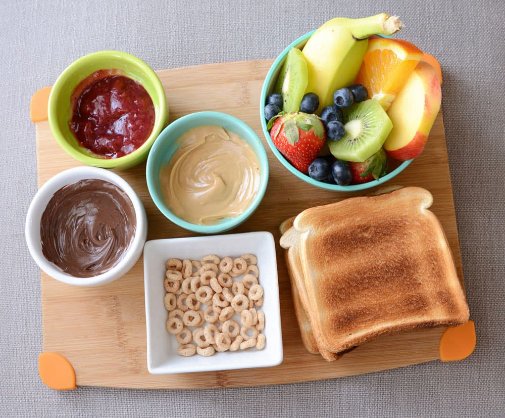 A tray with required ingredients: nut butter, chocolate-hazelnut spread, jam, fresh fruit and toast.