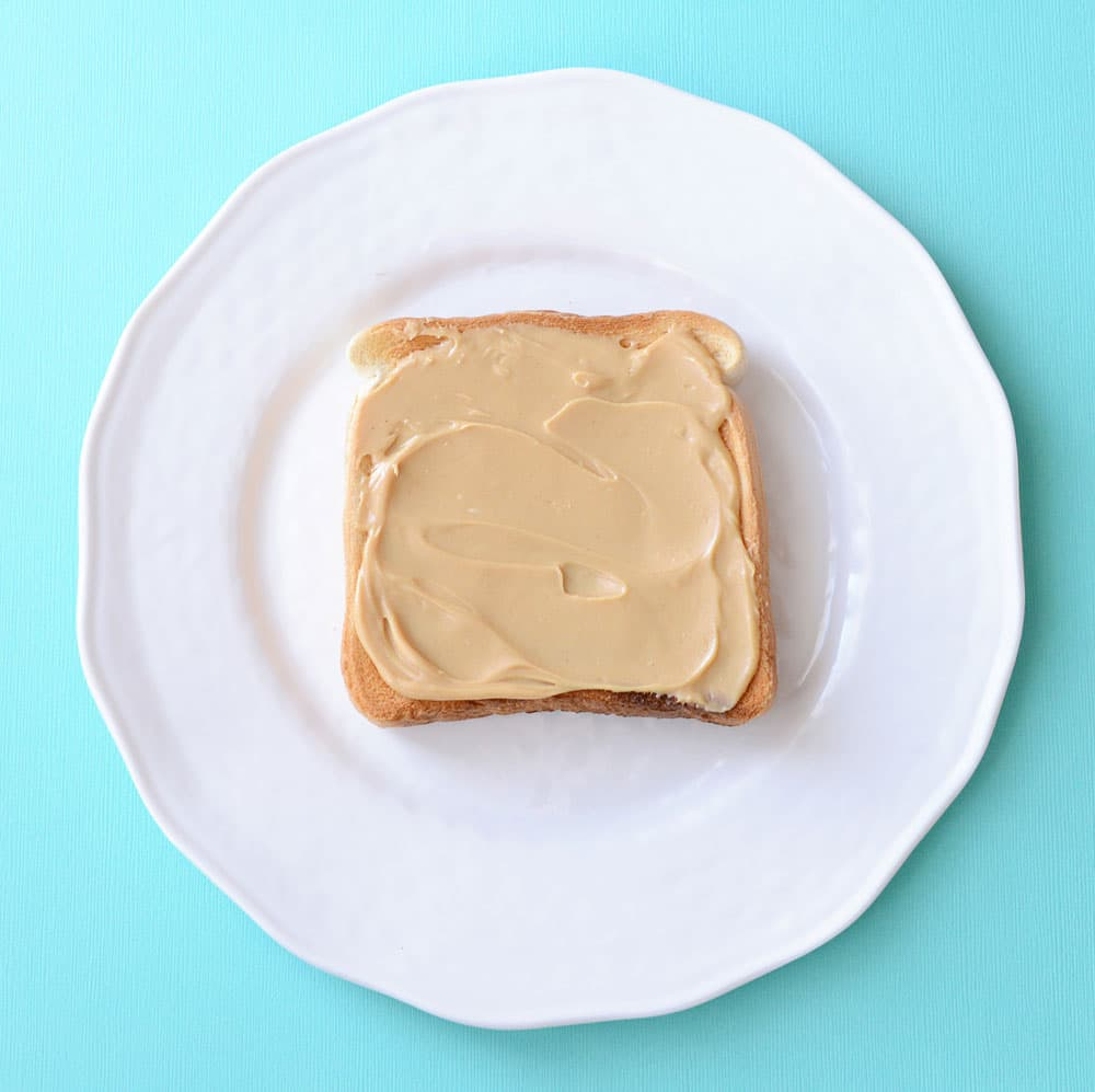A piece of toast covered with peanut butter.