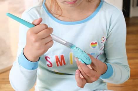 Little girl paints kindness rocks.