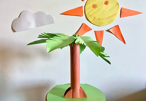 completed paper palm tree in front of a paper cloud and paper sun