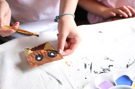 Folded paper plates owls get painted.