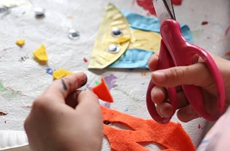 Little kid holds a pair of scissors to cut a felt beak.