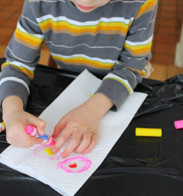 Child drawing on paper towel with markers.