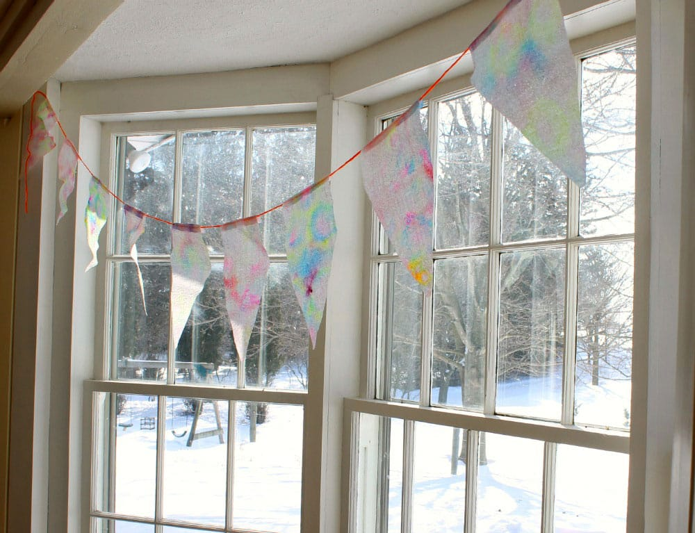 String of paper-towel bunting hanging in front of a bright sunny window.