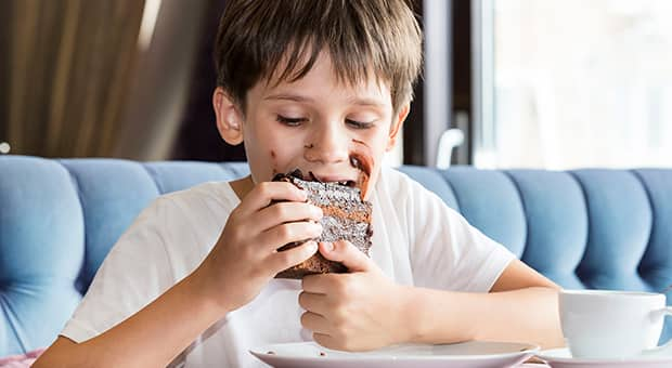 Boy eating cake with hands