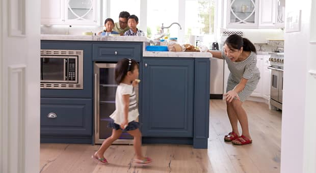 mother asking child to come to the dinner table, where her siblings and dad are already seated