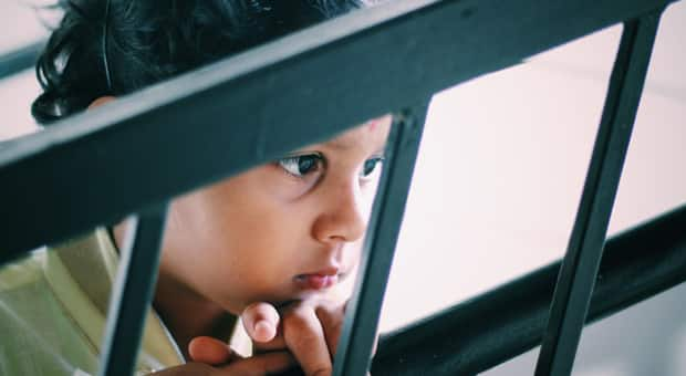 a child looking through a gate with an anxious look on their face