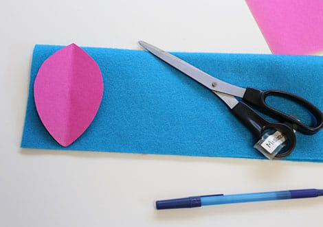 A feather-shaped cardboard template laid out on top of a blue piece of felt.