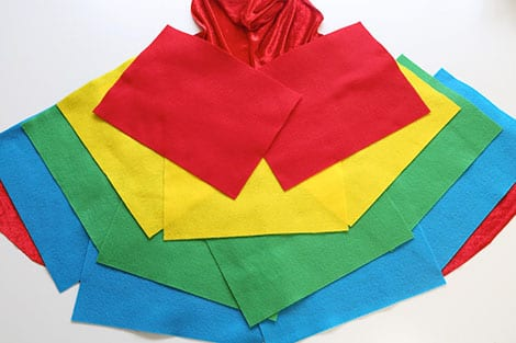 The cape laid out on a table, with pieces of felt laid out on top.