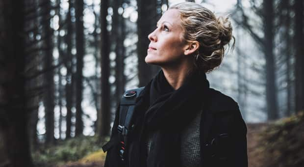a woman is hiking through the forest with beautifully pulled-back hair and an introspective look on her face