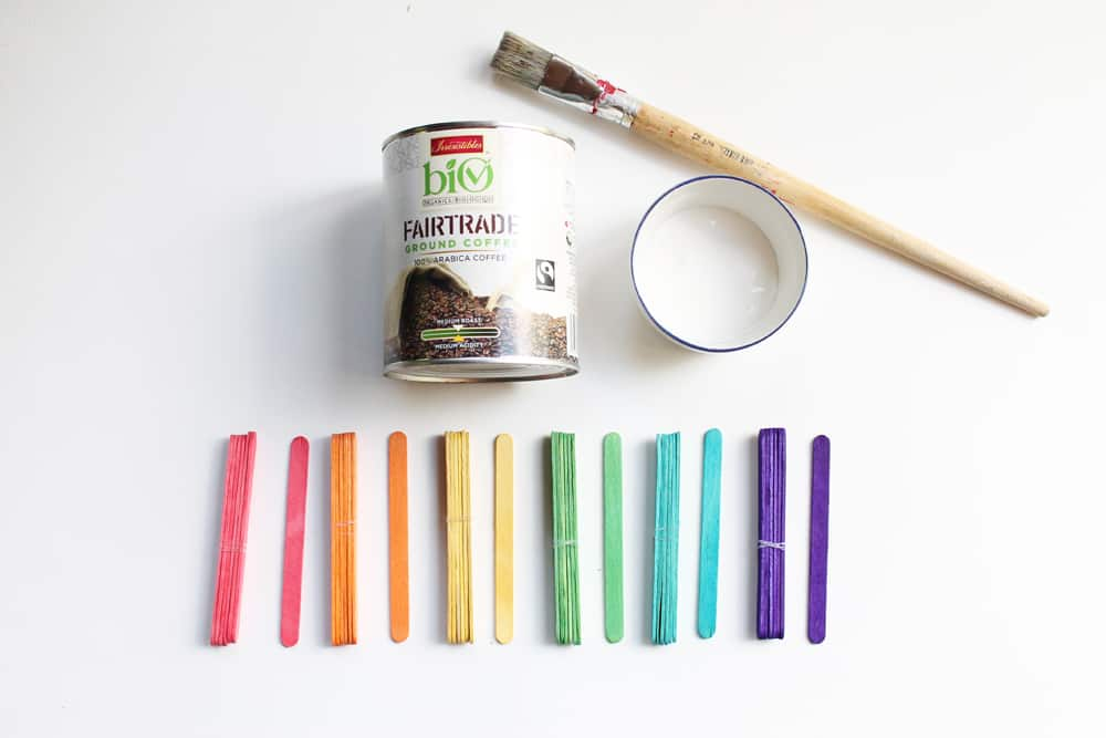 An empty bean can, paintbrush, rainbow-coloured popsicle sticks and white glue.
