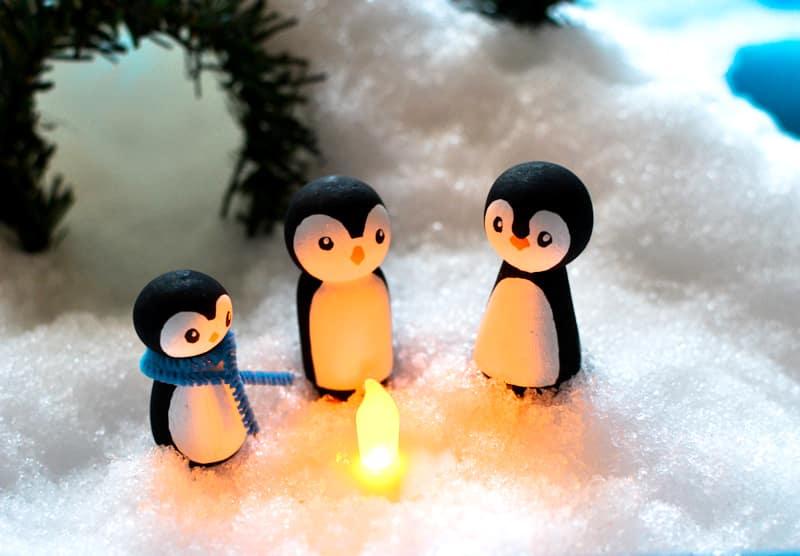 Penguins huddle around a LED tealight
