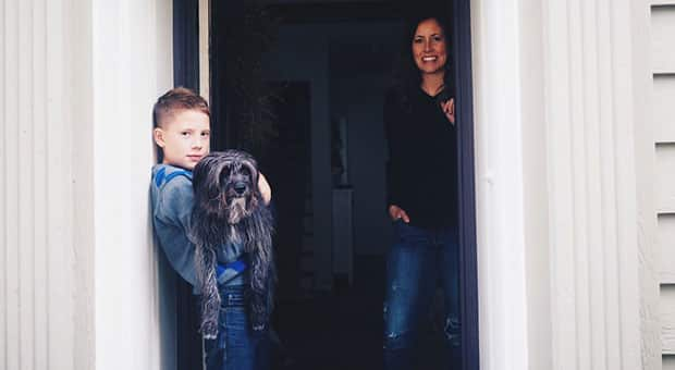 Woman and son stand by front door of their house