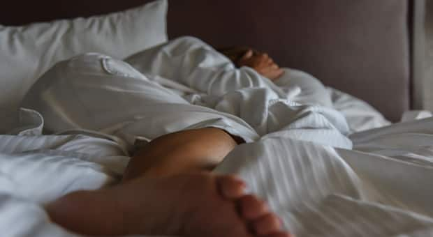 A woman lies in bed covering her face