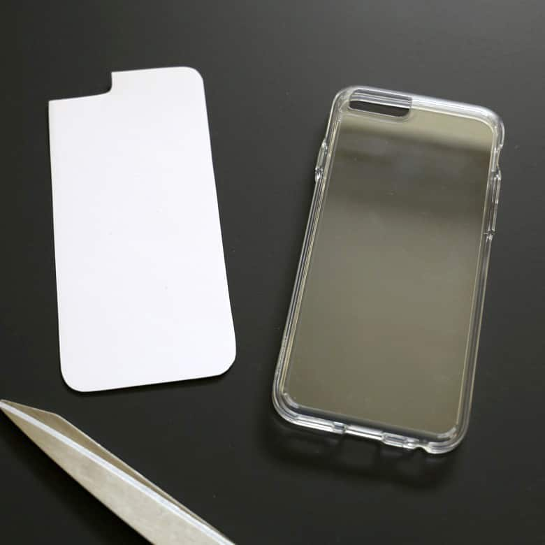 The card stock has been traced and cut out to fit the phone case. The top corner has been snipped off with a curved corner edge to allow for the camera lens on the phone.