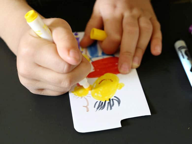 A child drawing a family portrait on the cell-phone case insert.