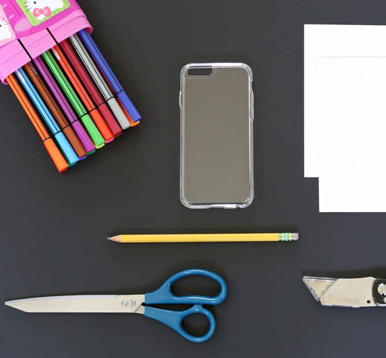 The supplies list laid out: clear cell-phone case, a piece of white card stock paper, pencil, pair of scissors, markers and a small utility knife.