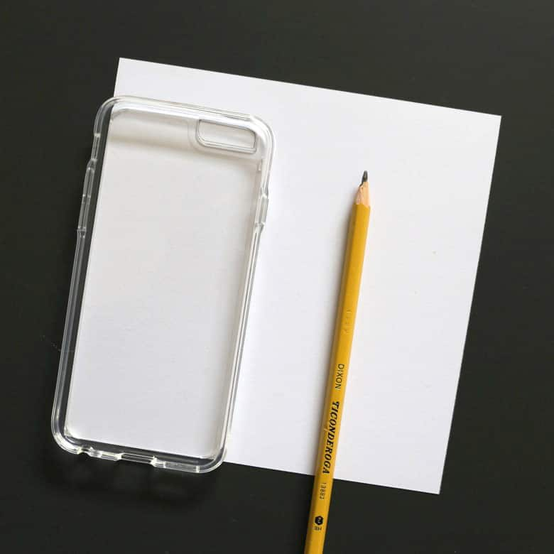 Clear cell-phone case lying on a piece of blank white card stock paper with a pencil beside it. The paper is lined up with two straight edges of the case.