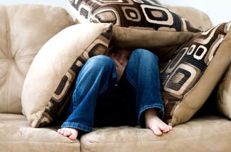 Little boy in pillow fort.