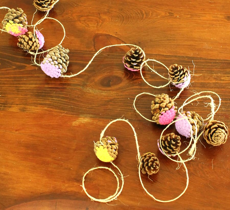 Painted pinecones strung together with twine.