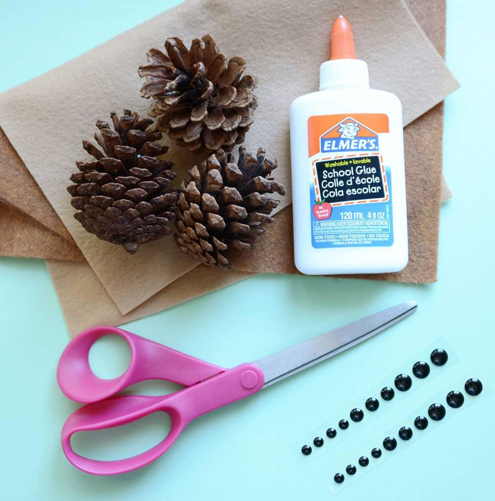 Pine cones, felt, scissors, glue and black enamel sticker beads