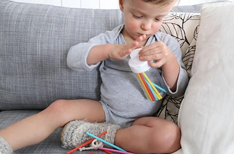Child sits on couch while focused on the colourful straws in a container.