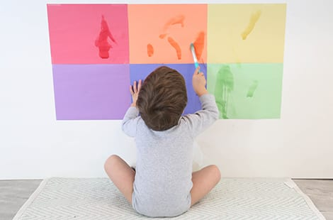 Child uses paint brush to