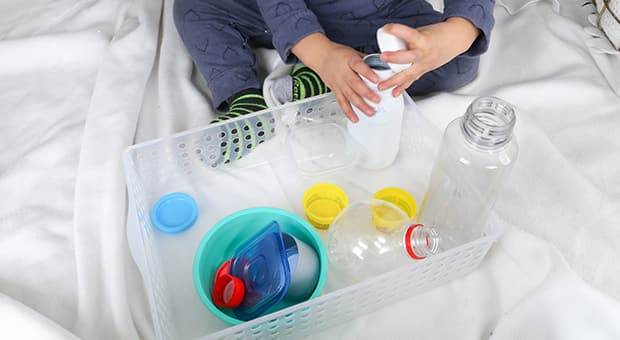 Child interacts with empty containers and bottles.