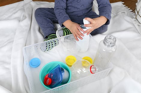 Child plays with various containers and bottles with and without lids.