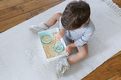 Child plays with dry oatmeal in containers.