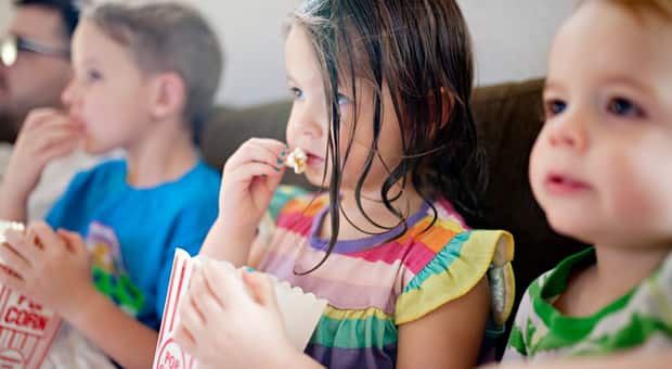 children sit eating delicious popcorn