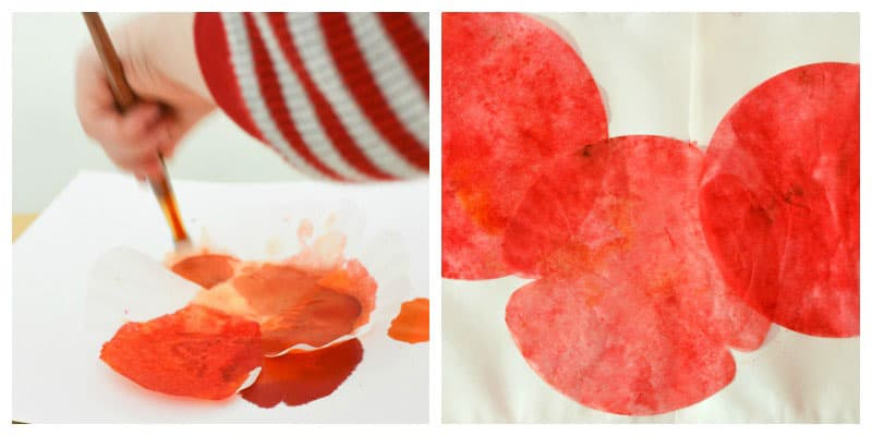 A child paints coffee filters with bright red paint.
