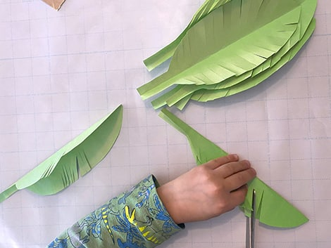 Cutting diagonally into the folded cut out leaf on the open side, making sure not to cut all the way through the fold