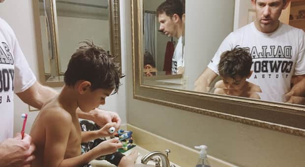 Father and son brush their teeth in the bathroom together.