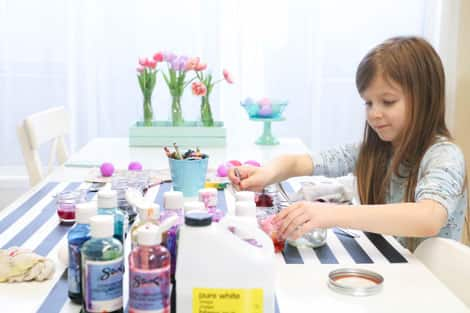 A young girl dip-dyeing her eggs.