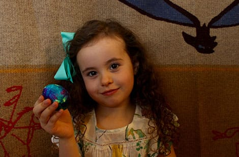 Little girl holds up finished tie-dyed egg.