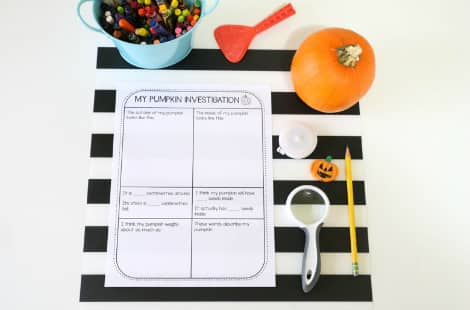 A bucket of crayons, pumpkin scooper, mini pumpkin, measuring tape, pencil, magnifying glass and 'My Pumpkin Investigation' sheet on a white tabletop