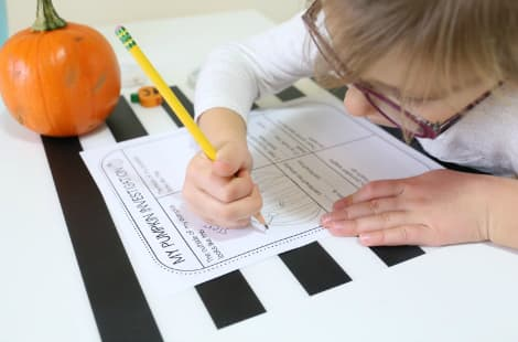 A child draws what the pumpkin to their right looks like on the 'My Pumpkin Investigation' sheet