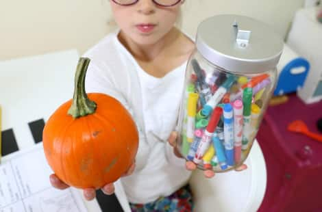 A child holds the pumpkin in one hand and a glass jar of markers in the other, comparing their weight