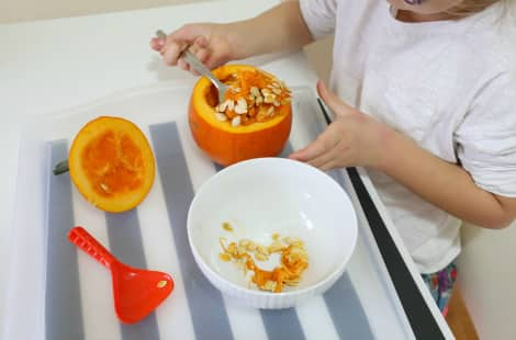 A child scoops the mini pumpkin's seeds into a bowl
