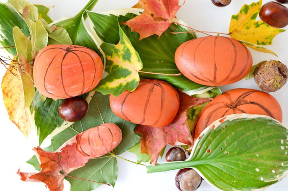 Striped pumpkin rocks among leaves and maple keys.